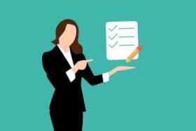 Nainen mustassa jakkupuvussa osoittaa paperia, jossa on pari riviä tekstiä ja merkkejä. Kynällä tehdään merkkejä.